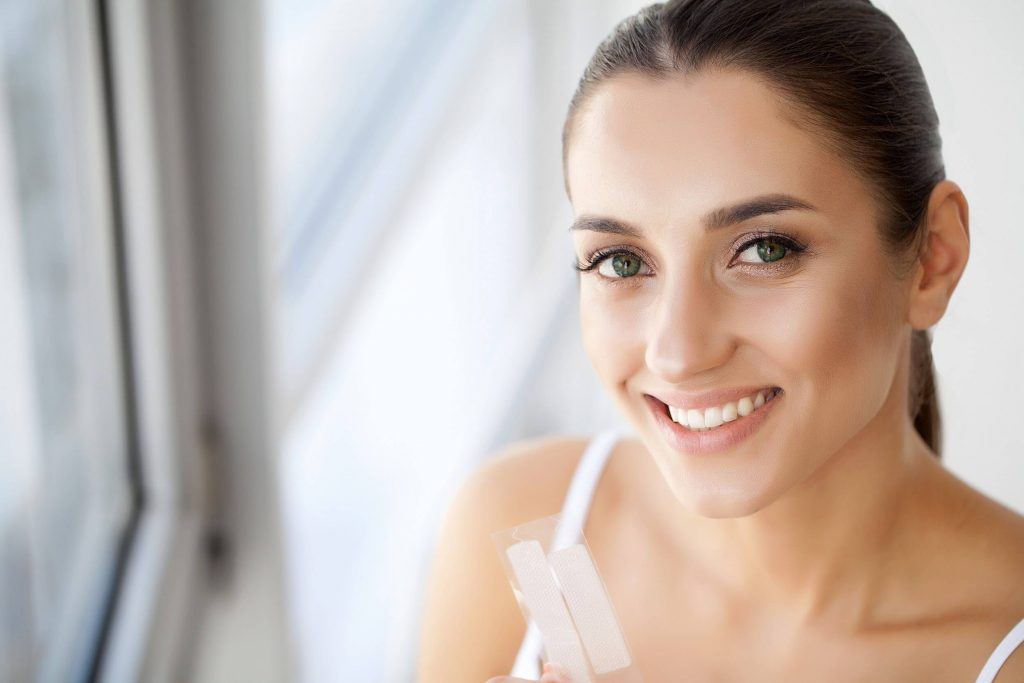 woman with white teeth holding whitening strips